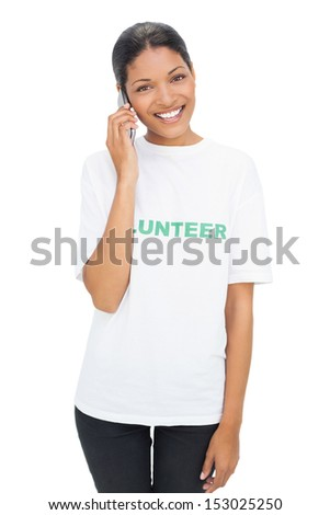 Happy model wearing volunteer tshirt on white background having a phone call - stock photo
