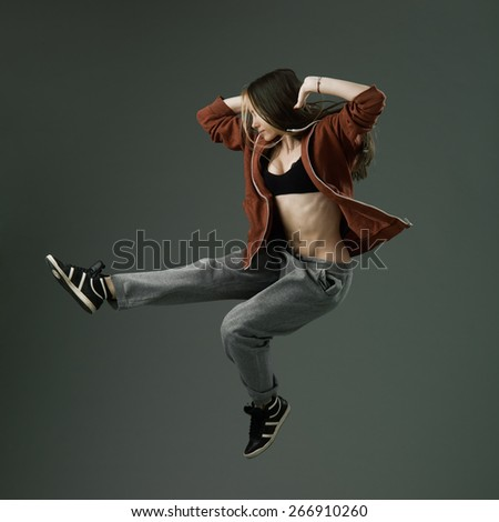 happy modern style dancer jumping against grey studio background - stock photo