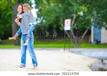 Happy mom and adorable little girl enjoying summer vacation - stock photo