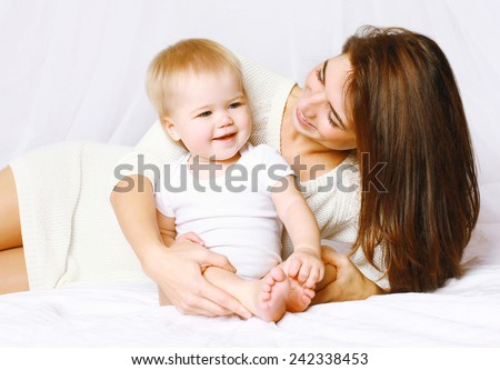 Happy mom and baby having fun in bed at home, life moment