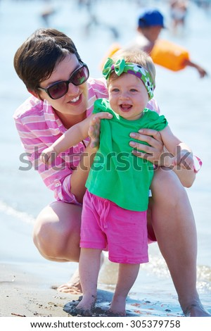 happy mom and baby on beach  have fun while learning to walk and  make first steps