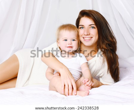 Happy mom and baby on the bed at home