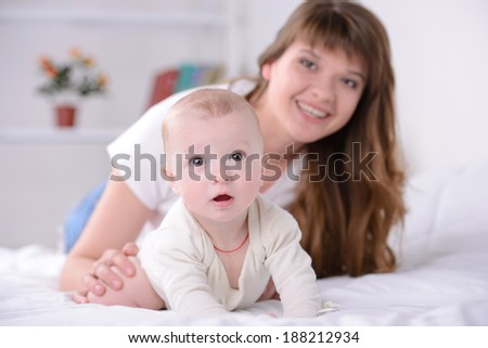 happy mom and baby playing on the bed at home