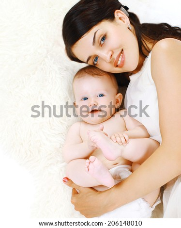Happy mom and charming baby lying in the bed, sleep, bedtime, top view - stock photo