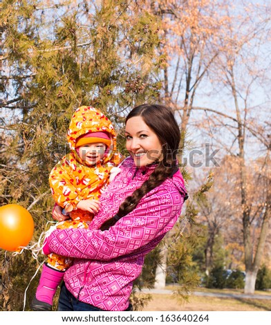 Happy mom and child boy hugging in leaves at fall  The concept of childhood and family  Beautiful Mother and her baby outdoors - stock photo