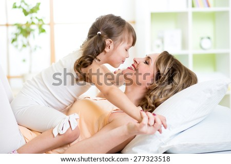Happy mom and child daughter embracing and kissing in bed - stock photo