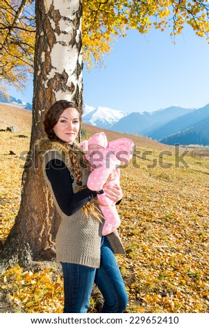 Happy mom and child girl hugging on nature at  fall. The concept of childhood and family. Beautiful Mother and her baby outdoor - stock photo