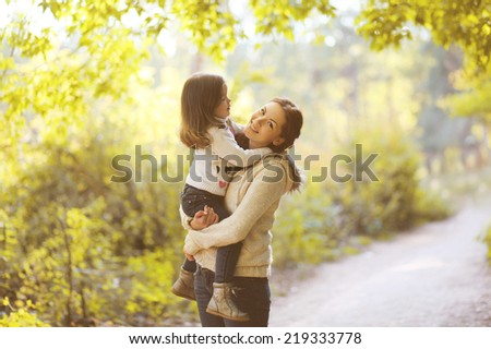 Happy mom and child in autumn park - stock photo
