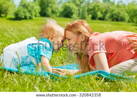 Happy mom and child with foreheads close together - stock photo