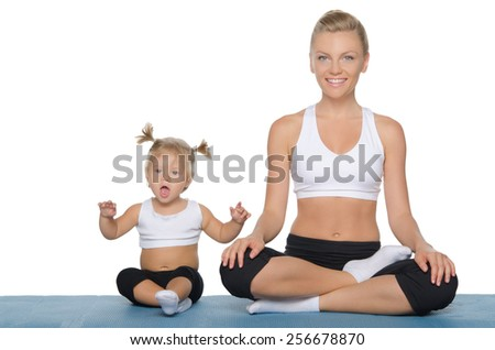 Happy mom and daughter engage in fitness on blue mat - stock photo