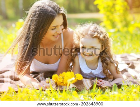 Happy mom and daughter having fun in summer day