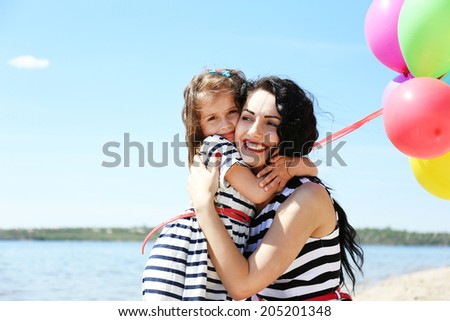 Happy mom and daughter on the beach - stock photo