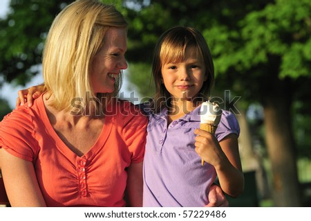 happy mom and daughter sharing an ice cream in the park