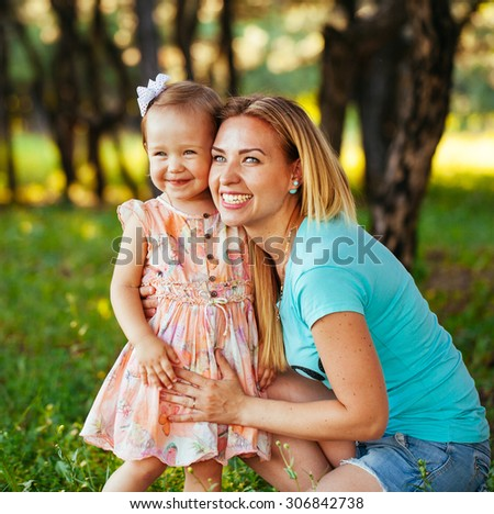 Happy mom and daughter smiling at nature.  - stock photo