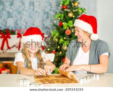 Happy mom and daughter stretching the christmas cookie dough together, baking Christmas gingerbread cookies at home, with Santa Hats, chimney and Christmas Tree with lights.  - stock photo