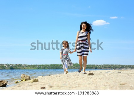 Happy mom and daughter. Walk on the beach - stock photo