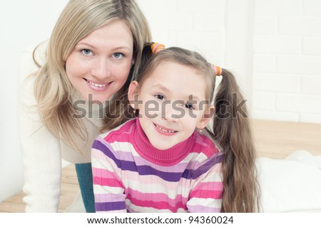Happy mom and her daughter playing on the floor and looking at camera