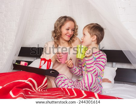 Happy mom and her son having breakfast in big bed on Mother's Day - stock photo