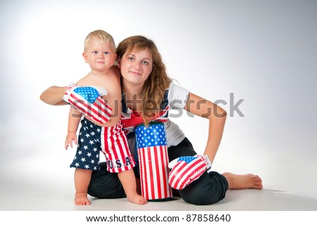 Happy mom and son. Boy in boxer shorts with  boxing gloves and pear. - stock photo