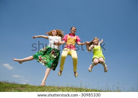Happy Mom and two daughter jumping on green meadow