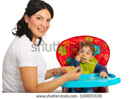 Happy mom feeding her baby boy with vegetables puree - stock photo