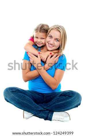 Happy mom sitting on floor while daughter hugging her from behind.