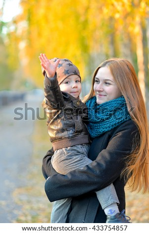 Happy mom with a cheerful kid on autumn walk in the park.