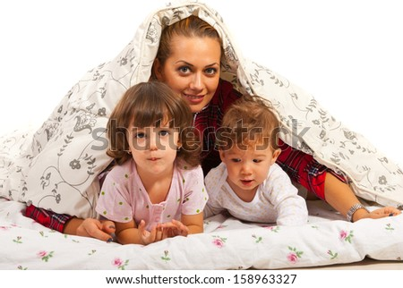 Happy mom with two kids in bed having fun