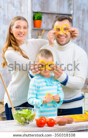 Happy moment. Pleasant overjoyed family holding slices of pepper on their eye and cooking salad while having fun in the kitchen - stock photo