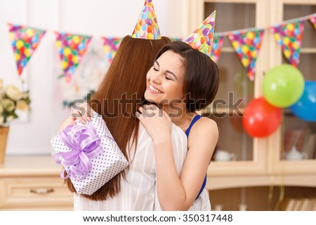 Happy moment. Young nice-looking birthday girl is hugging her girl friend after receiving a present.  - stock photo