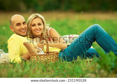Happy moments of new family concept. Portrait of beautiful young couple having picnic in countryside. Smiling man and woman in trendy casual clothing with italian wine & bread in basket. Outdoor shot - stock photo