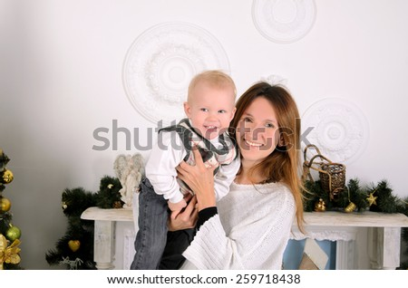 happy mommy holding little son in christmas interior  - stock photo