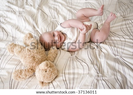 Happy 7 month old baby lying down next to teddy bear - stock photo