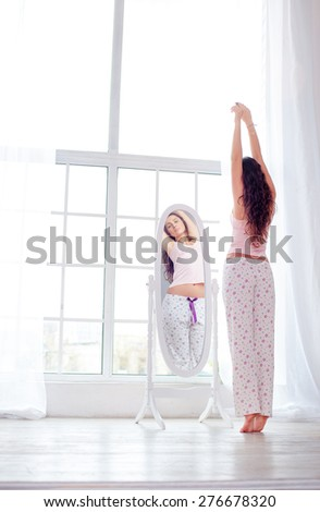 Happy morning. Attractive young woman stretching near mirror at her apartment. - stock photo
