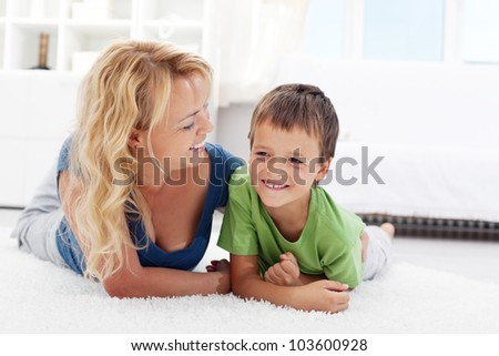 Happy morning - boy playing with mother on the sunlit floor - stock photo