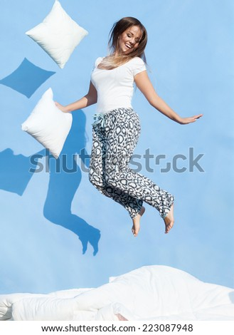 Happy morning concept, woman holding a pillow jumping up on bed - stock photo