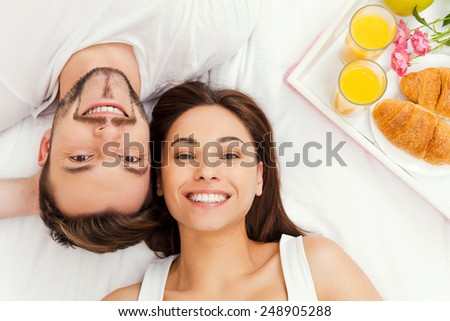 Happy morning. Top view of beautiful young loving couple lying in bed together and smiling while tray with breakfast laying near them - stock photo