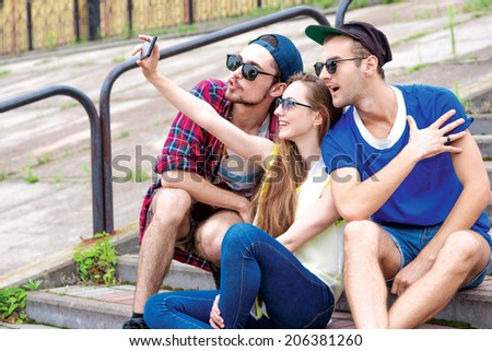 Happy morning with friends. Young friends have fun together on the street and smile at each other. Funny guys make Selfie - stock photo