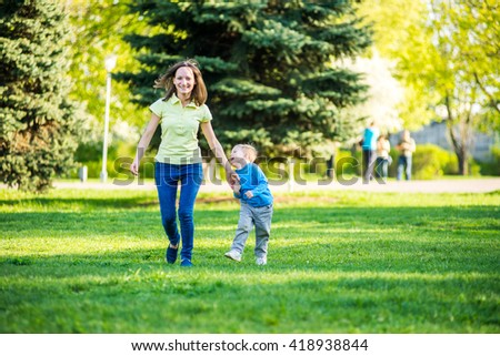 Happy mother and adorable little boy enjoying warm weather at beautiful park - stock photo
