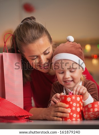 Happy mother and baby checking christmas purchases - stock photo