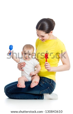 Happy mother and baby girl having fun with musical toy Isolated on white - stock photo