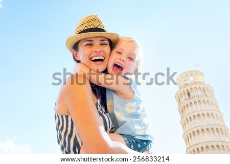 Happy mother and baby girl hugging in front of leaning tower of pisa, tuscany, italy - stock photo