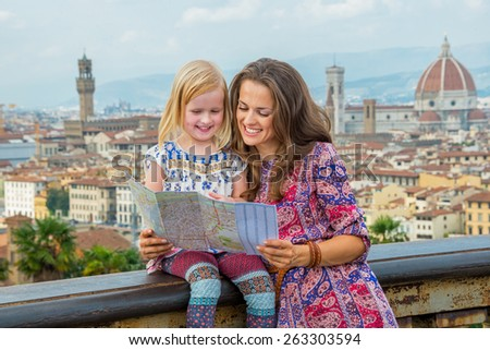Happy mother and baby girl looking at map against panoramic view of florence, italy - stock photo