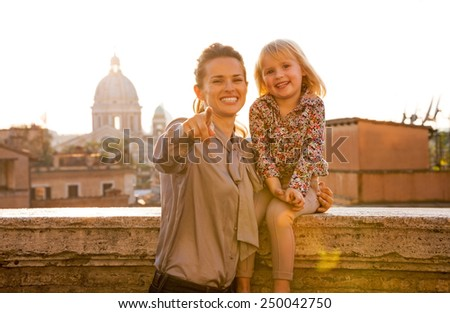 Happy mother and baby girl on street overlooking rooftops of rome on sunset pointing in camera