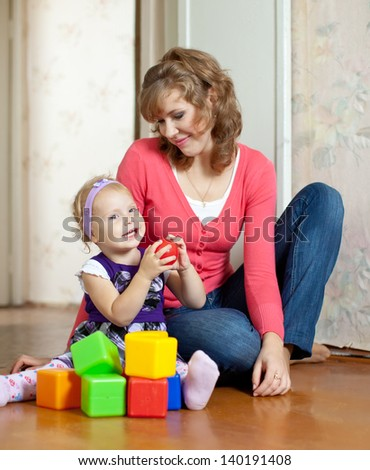 Happy mother and baby girl plays with toy blocks in home