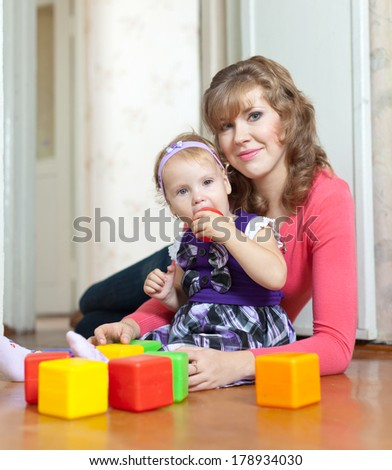 Happy mother and baby girl plays with toy blocks in home - stock photo