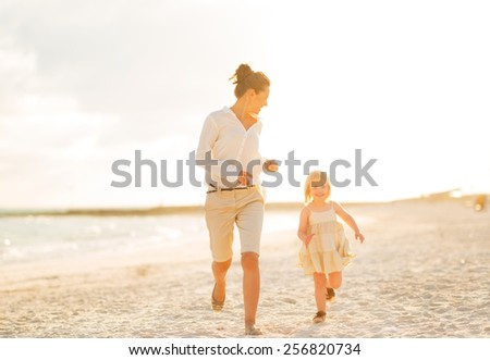 Happy mother and baby girl running on beach at the evening - stock photo