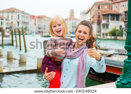 Happy mother and baby girl standing on embankment in venice, italy and showing thumbs up - stock photo