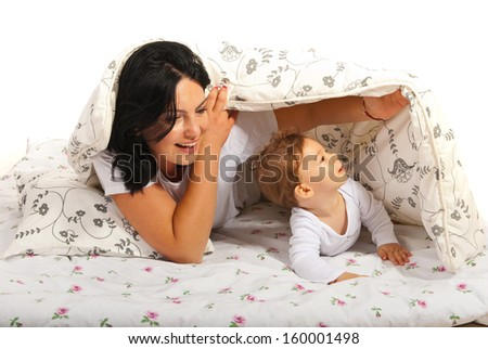 Happy mother and baby having fun in bed