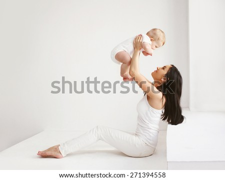 Happy mother and baby having fun together at home in white room - stock photo